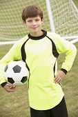 Portrait boy in goalkeeper's kit with ball