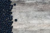 Dried aronia berries on wood