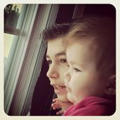 Brother and Sister looking out window together with instagram effect