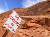 No Stopping Sign With Rock Face In Background