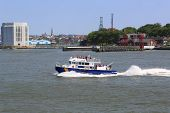 NYPD boat patrolling New York Harbor in the front of Governors Island