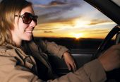 Young Woman Wearing Sunglasses Smiling And Driving