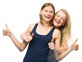 Two young happy women showing thumb up sign using both hands, isolated over white