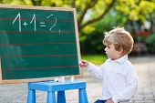 Little Boy At Blackboard Practicing Mathematics
