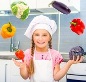 smiling little girl juggle vegetables home in the kitchen