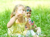 Girl And Boy Blowing Soap Bubbles