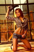 Young woman cowboy indoors portrait.