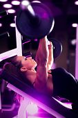 Young woman bodybuilder with barbell. Pink tint.