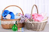 Colorful towels in baskets on table, on light background