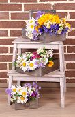 Beautiful flowers in crates on small ladder on brick wall background
