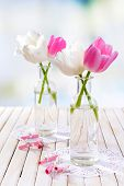 Beautiful tulips in bucket in vase on table on light background