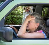 picture of blood drive  - Closeup of senior woman driver holding her head in frustration all stressed out - JPG