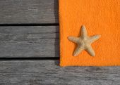 Beach towel and starfish on wood background. Concept of leisure and travel