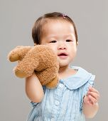 Baby girl holding her bear doll