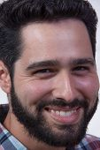 bearded young man smiling