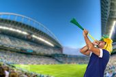 Brazilian fan at stadium playing vuvuzela for celebrating a brazil team goal