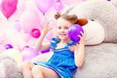 Cheerful girl plays with balloon in playroom