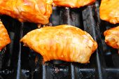 Close-up Of One Saucy Wing Piece Cooking On A Grill