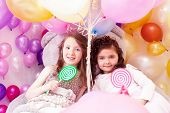 Beautiful sisters with lollipops posing at camera