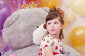 Dreamy girl posing on backdrop of teddy bear