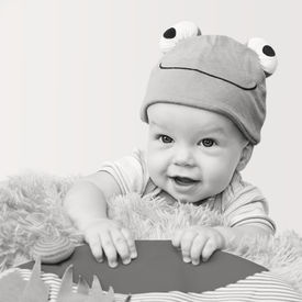pic of baby frog  - cute baby playing in the hat frog lying on his stomach on a white background  - JPG