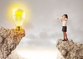 Businesswoman standing on the edge of rock mountain with an idea bulb on the other side