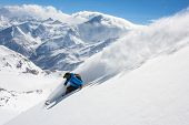 Skier in high mountains during sunny day.Freeride in fresh powder snow
