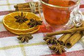 Anise Stars, Cassia Cinnamon Sticks, Dried Orange Rings And Fruit Tea On The Tablecloth