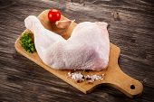 Raw chicken leg on cutting board on cutting background