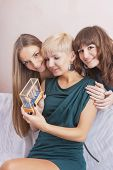 Three Young Caucasian Girls With Teeth Brackets Sitting Together Indoors. Holding Present
