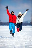 Young happy couple jumping outdoors. Cold winter season and snowfield.