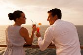 romantic young couple toasting with cocktail on cruise ship