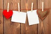 Photo frames and valentines toy hearts over wooden background