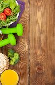 Dumbells, tape measure and healthy food over wooden background. Fitness and health. View from above