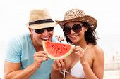 playful young couple with slice of watermelon on summer holiday