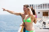 loving young couple on cruise and pointing at sea