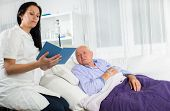 Nurse reading a book to his patient
