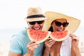 portrait of happy couple enjoying watermelon on summer holiday