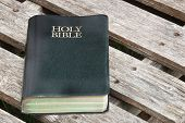 stock photo of bible verses  - Holy Bible closeup on old wood seat - JPG