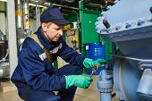 stock photo of manufacturing  - service engineer worker at industrial compressor refrigeration station repairing and adjusting equipment at manufacturing factory - JPG