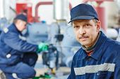 picture of manufacturing  - portrait of service engineer worker at industrial compressor station for refrigeration at manufacturing factory - JPG