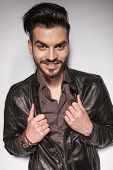 Portrait of a young casual man smiling at the camera while pulling his leather jacket.