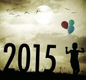 Retro old fashioned photo of kid with balloons running on summer meadow celebrating new 2015 year