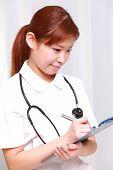 nurse fills medical chart