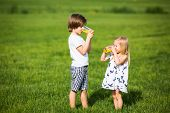 stock photo of little boys only  - Little boy and little girl standing on a green lawn and drinking juice - JPG