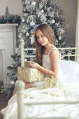 stock photo of preteen  - Preteen child girl wake up in her bed near decorated Christmas tree in beautiful hotel room in the holiday morning - JPG
