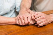 Senior couple holding hands on table at home in the kitchen