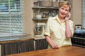 Senior woman on the phone at home in the kitchen