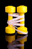 Two Yellow Dumbbells And Tape Measure Placed Vertically With Reflection Isolated On Black Background