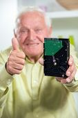 Senior man holding hard disk in the living room